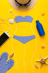 Outlines of girl in paper swimsuit drawing by chalk. Beach accessories. Top view. Flat lay. Summer travel and sun protection concept. Origami. Mock-up