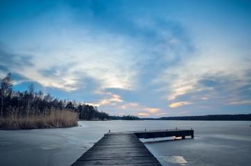 Evening winter landscape. Wooden pier over a beautiful frozen lake.