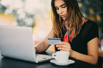 Selective focus of woman using credit cart and laptop for shopping while sitting in cafe.