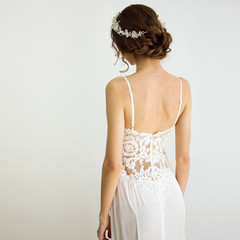 young brunette sexy girl in a white wedding boudoir dress and jewellery in hairstyle is standing from the back  like swan princess on a white wall background