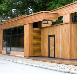 A clean wooden facade of a shop near a road in the background of a tree