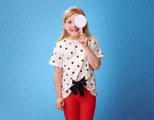 child with covered one eye taking visual acuity test on blue