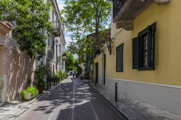 Plaka, Athens / Greece - April 20, 2018: Narrow alley in Plaka area under the Acropolis of Athens. Historic center of Athens city. Sunny day with cloudy sky