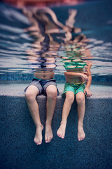 kids legs dangling underwater pool
