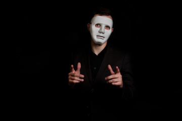 A man stands on a black background in a white mask. Makes a gesture, holding out his hands and pointing with his finger