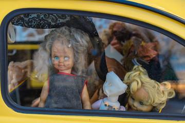 old broken dolls in the car window