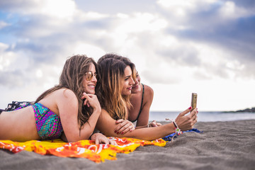 three nice caucasian long hair beautiful woman 25 years old lay down at the beach using a cellular smartphone to send picture to friends or check social networks with outdoor wifi connection