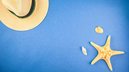 straw hat and starfish on a blue background. Top view Copyspace