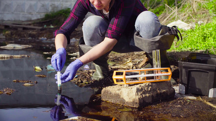 Close up hands of woman scientist ecologist taking sample of the water from the big dirty puddle near garbage dump.