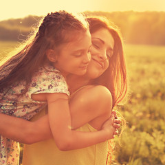 Happy enjoying mother strong hugging her relaxing kid girl on sunset bright summer background with closed eyes. Closeup toned orange color portrait of family love.