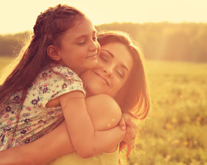 Happy enjoying mother strong hugging her relaxing kid girl on sunset bright summer background. Closeup toned color portrait of love.