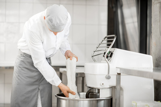Man mixing dough with professional kneader machine at the manufacturing