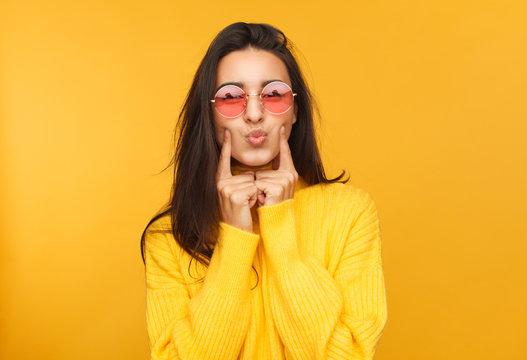 Woman in sunglasses touching cheeks