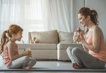 Profile of beautiful lady and daughter sitting on carrymats and holding glasses with orange drinks. They are looking at each other full of joy and amusement. Grey couch at the background