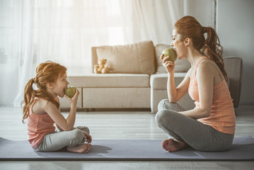 Profile of woman and kid after aerobics. They are sitting in front of each other on the floor and biting green apples with smile