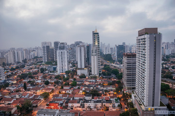 View of the city skyline in the early morning light with houses and buildings under cloudy skies in the city of São Paulo. The gigantic city, famous for its cultural and business vocation.