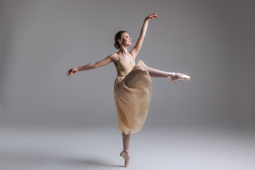 Dance to inspire! Full length side view of the classical ballet dancer performing ballet movements on the isolated background.