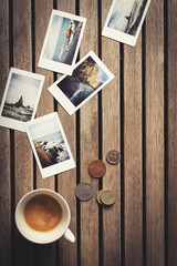 Top view of some instant photographs on a wooden coffee shop table. An espresso and several coins to pay cash on the table. Flat lay image.