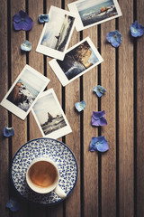 Flat lay image of several instant photographs, an espresso and some blue petals on a wooden coffee house table.Planning the honeymoon trip. Give a trip.