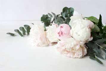Styled stock photo. Decorative still life floral composition. Wedding or birthday bouquet of pink and white peony flowers and eucalyptus branches. White table background.