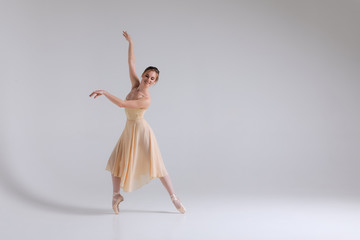 Dialogue of dance! Full length picture of the smiling delicate full of tenderness ballerina standing in pointe position.