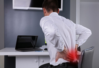 Business man suffering from back and neck pain in an office. Incorrect sitting posture problems, Muscle spasm, rheumatism. Pain relief, chiropractic concept