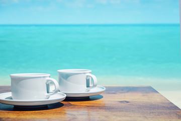 Two cups of coffee over a clear ocean's water