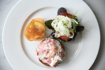 Lobster roll with salad and potato chips on plate