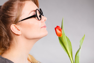Smiling lady sniffing flower.
