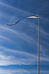 Flag of Estonia against the sky. A thin horizontal ribbon style flag in the wind