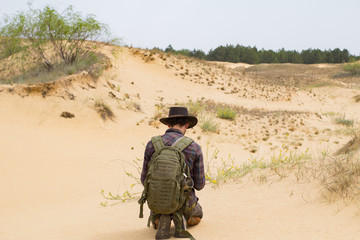 Young male traveler in desert, hipster photographer in hat make photo