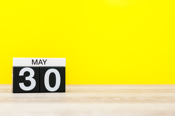 May 30th. Day 30 of may month, calendar on yellow background. Spring time, empty space for text