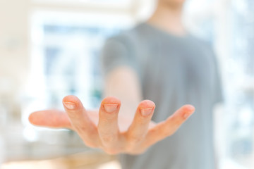 Man holding his hand out and showing something in a bright room