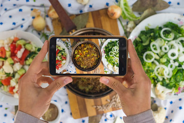 Smartphone photography of food. Woman hands take phone photography of lunch or dinner. Russian traditional buckwheat porridge cooked in pot. Good for social media publications or blogging.