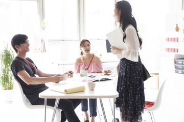 オフィスで資料を持ち楽しそうに会話する女性