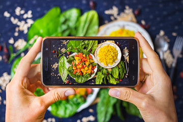 Smartphone photography of food. Woman hands take phone photography of fresh vegetables salad and Arabian bulgur for lunch or dinner. Good for social media publications or blogging.