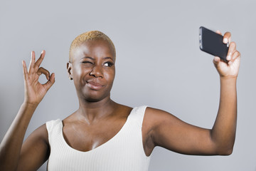 young beautiful and happy black afro American woman smiling excited taking selfie picture portrait giving ok hand sign blinking eye