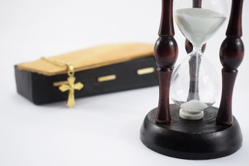 an hourglass and a coffin on a white background, time and death