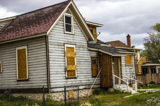 Abandoned Home In Disrepair With Boarded Up Windows