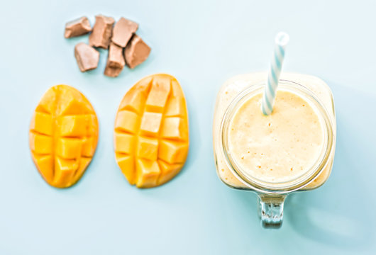 summer drink mango milkshake in mason jar with drinking straw decorated with a half of mango, chocolate pieces flat lay top view on blue background