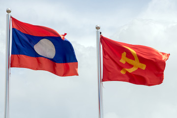 Lao National Flag with red flag with communist symbols of a sickle with a hammer flying in a blue sky, Laos