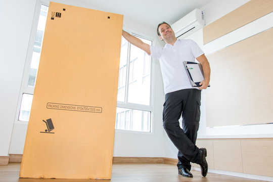 A man standing beside a large package in an empty room. The postman delivers the parcel to the new apartment.