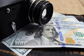 earnings in photography, a camera and money (dollars) are on the table
