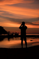 Silhouette of Man taking a sunset with a smartphone at Loh Dalum Bay, Phi Phi Island, Krabi, Thailand.