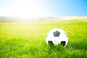 Soccer ball or football ball on ground and green field of grass