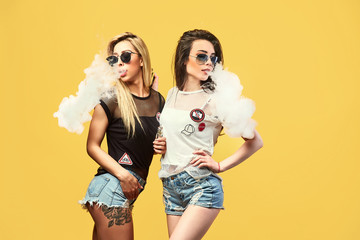Side view of trendy young female in glasses and shorts standing and smoking on studio background Wall mural