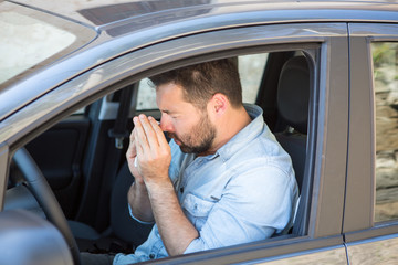 Man reacts with pollen on hay fever in a car