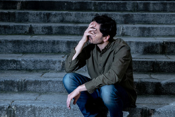 depressed man sitting out side on steps feeling tired and sad.