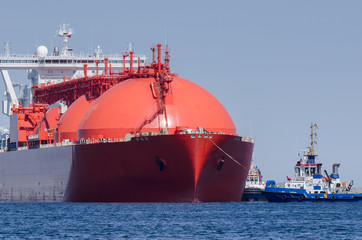 LNG TANKER - The red ship enters port with assurance of tugs