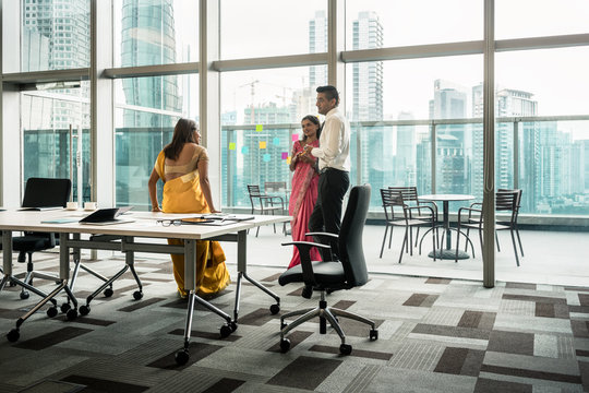 Three Indian employees talking during break in the meeting room of a modern business building